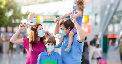 Sicheres Reisen trotz Corona - Familie mit Masken am Flughafen