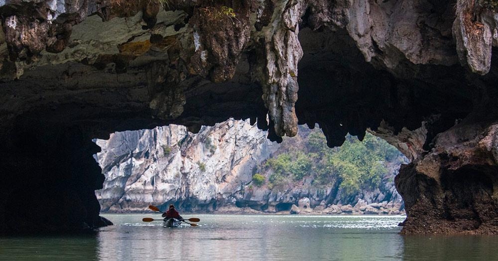 Vinh Ha Long - Kajak fährt unter einem Kalkgesteinbogen durch