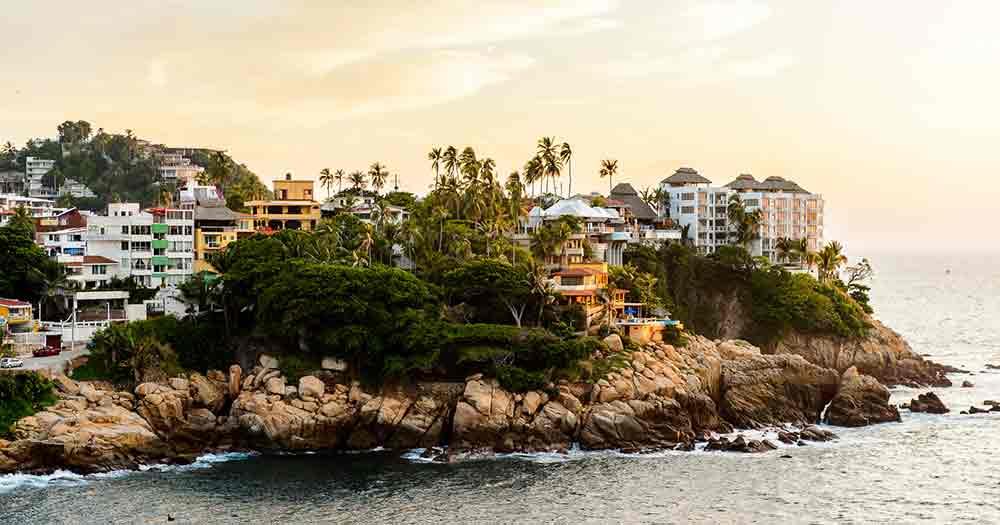 Acapulco - Blick vom Meer auf einen Felsenvorprung an der Küste